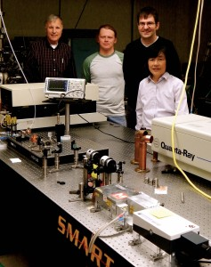 Bill Fairbank, Sam Ronald, Dylan Yost and Siu Au Lee (Left to Right) pose in front of the Lyman Alpha source early in its development.